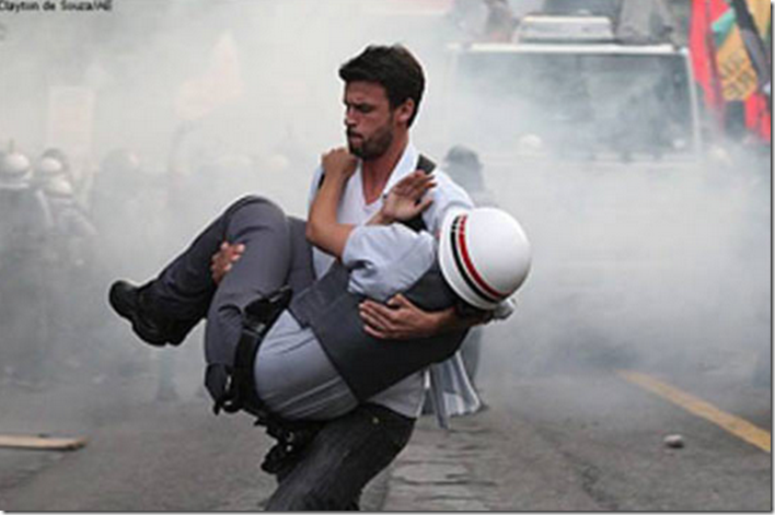 11. Sao Paulo, Brazil, 2012 - Brazilian protester carrying an injured officer to safety