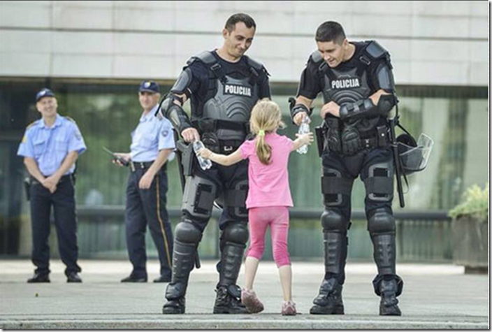 12. Bosnia, 2013 - Girl hands water to two officers