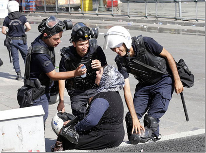 13. Ankara, Turkey, 2013 - Riot police help a womanaffected by tear gas