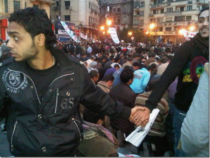 15. Cairo, Egypt, 2011 - Christians protecting Muslims as they pray during the revolution