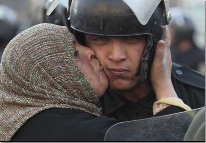 16. Egypt, 2011 - Egyptian woman kisses a policeman during the revolution against the Mubarak Government