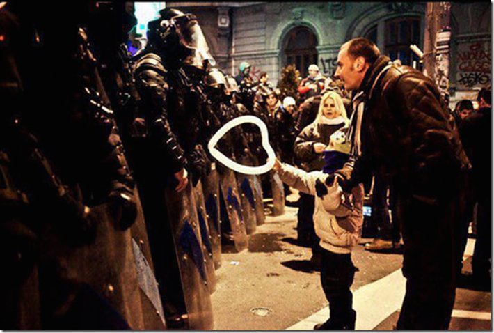 19. Bucharest, Romania, 2012 - A young boy offers a heart-shaped baloon to police. 1