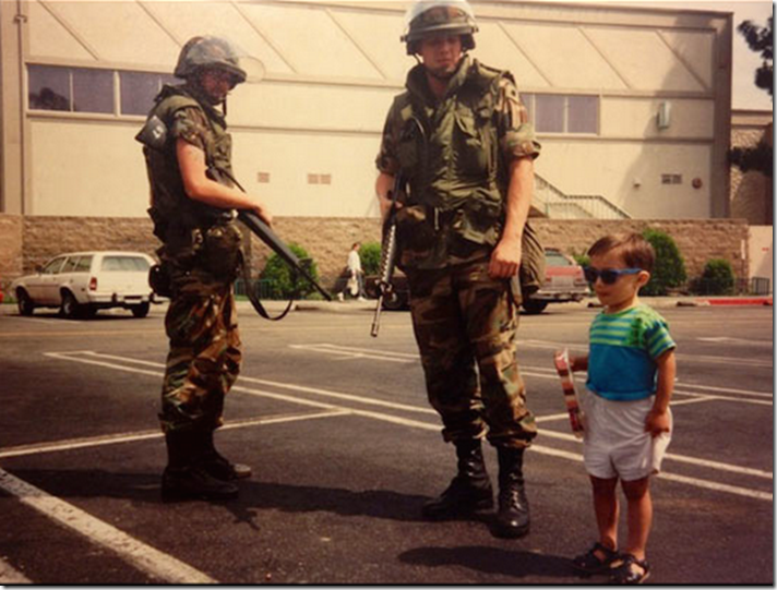 2. Los Andeles, USA, 1992 - A child poses beside National Guard members during The LA Riots