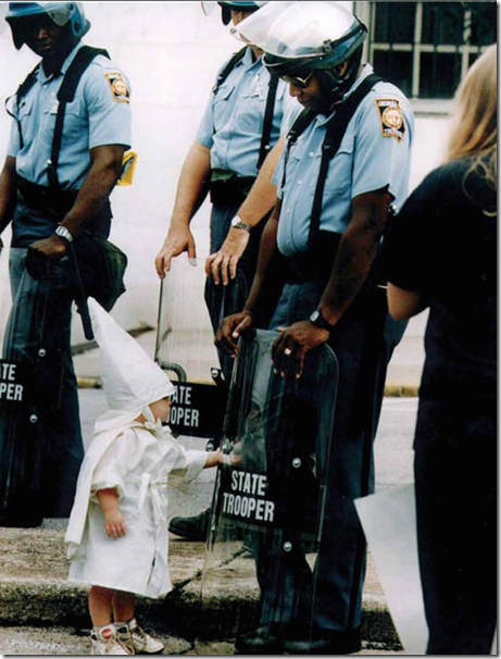 3. Georgia, USA, 1992 - Child touches his reflection during a KKK demonstration