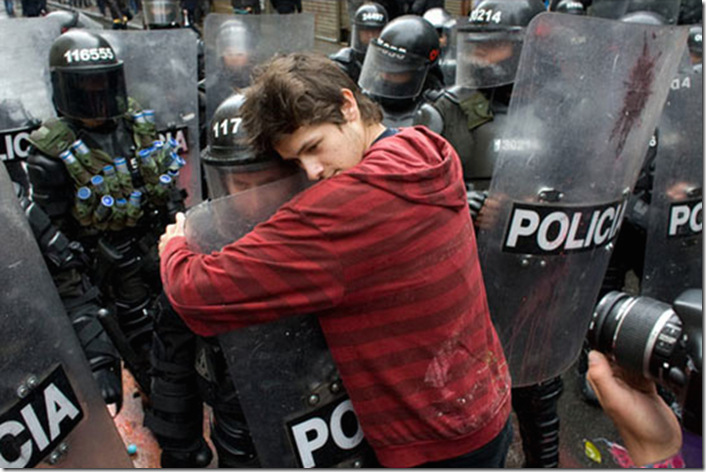 5. Bogota, Colombia, 2011 - A student protesting education reform hugs a policeman