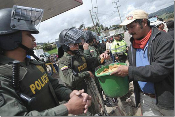 6. Columbia, 2013 - Protestors share crackers with colombian riot police
