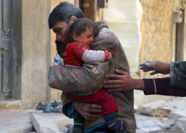 A boy rescues his sister from Syrian rubble.