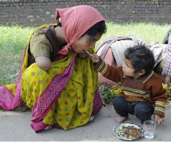 A handicapped mother being offered food from her child.