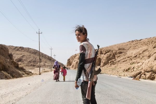 Yezidi girl carries an assault rifle to protect her family from ISIL.